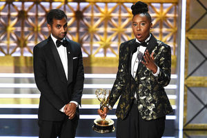 Brown man in black-and-white tuxedo stands next to Black woman