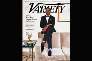 Black man in black tuxedo with purple socks and white shirt on brown couch next to gold statue on green glass table in front of beige wall