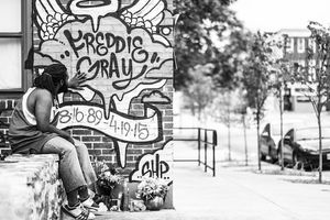 Black-and-white photo of Black man in tank top, pants and sneakers sitting on stone ledge while touching multicolored mural on brick wall in front of grey sky