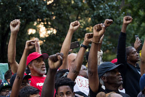 A crowd of Black men raise their fists in protest