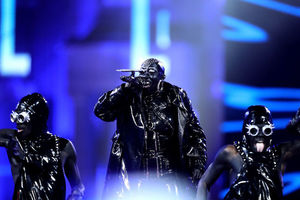 Black woman in black body paint and black and silver outfit stands between Black women in black body paint and black and silver outfits in front of blue screen