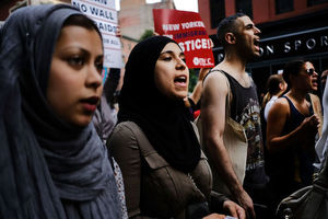 Brown women in black and navy hijabs stand next to Brown women and men in multicolored clothing holding white and red signs in front of brown and grey buildings and grey sky