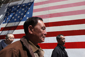 Three Asian-American men in multicolored clothing walk in front of white wall with red and white and blue U.S. flag mural