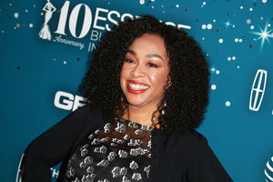 Black woman in black sweater and black blouse with grey and white pattern stands in front of blue wall with white text and insignia