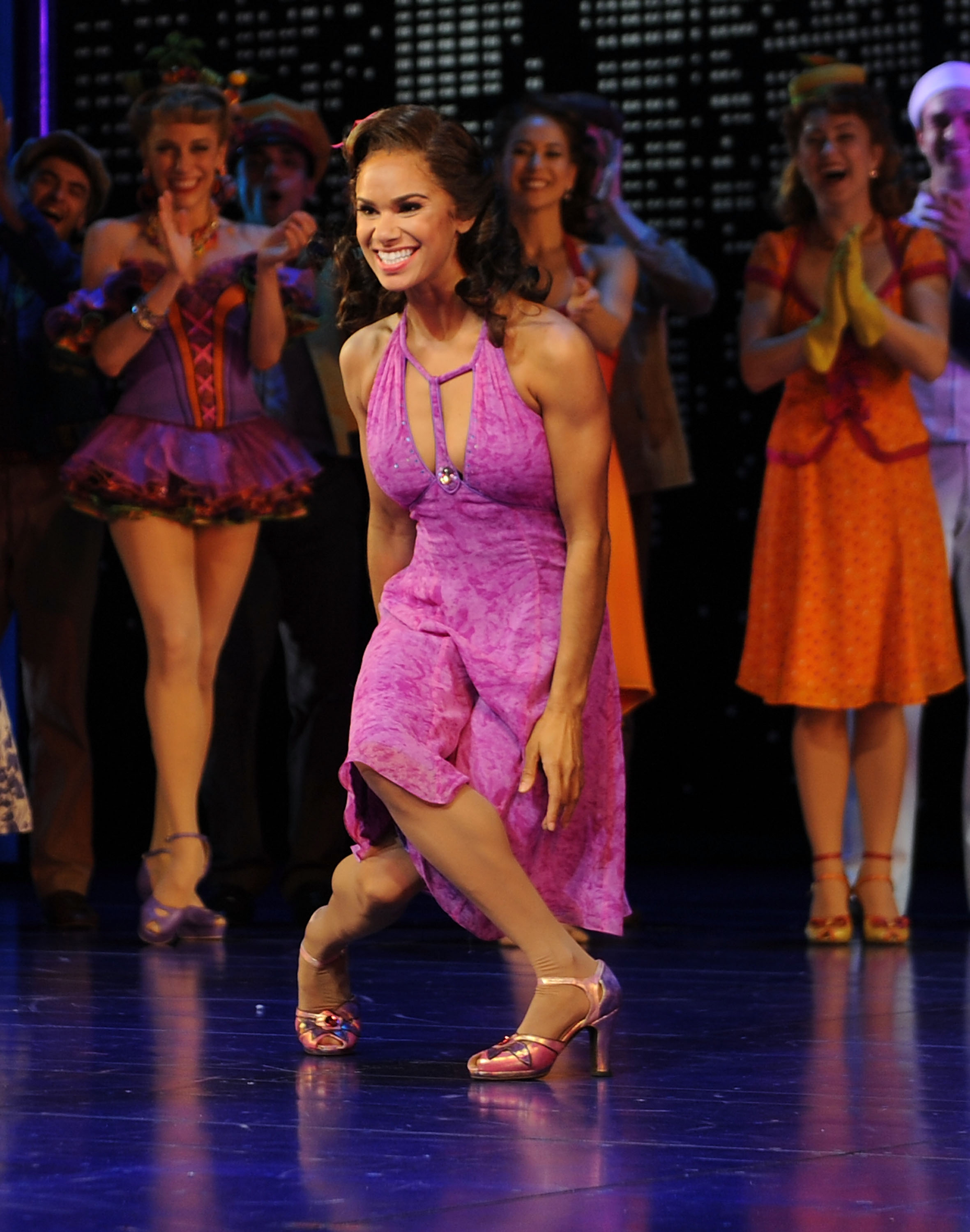 A photo of Misty Copeland taking a bow in a purple dress on a Broadway stage