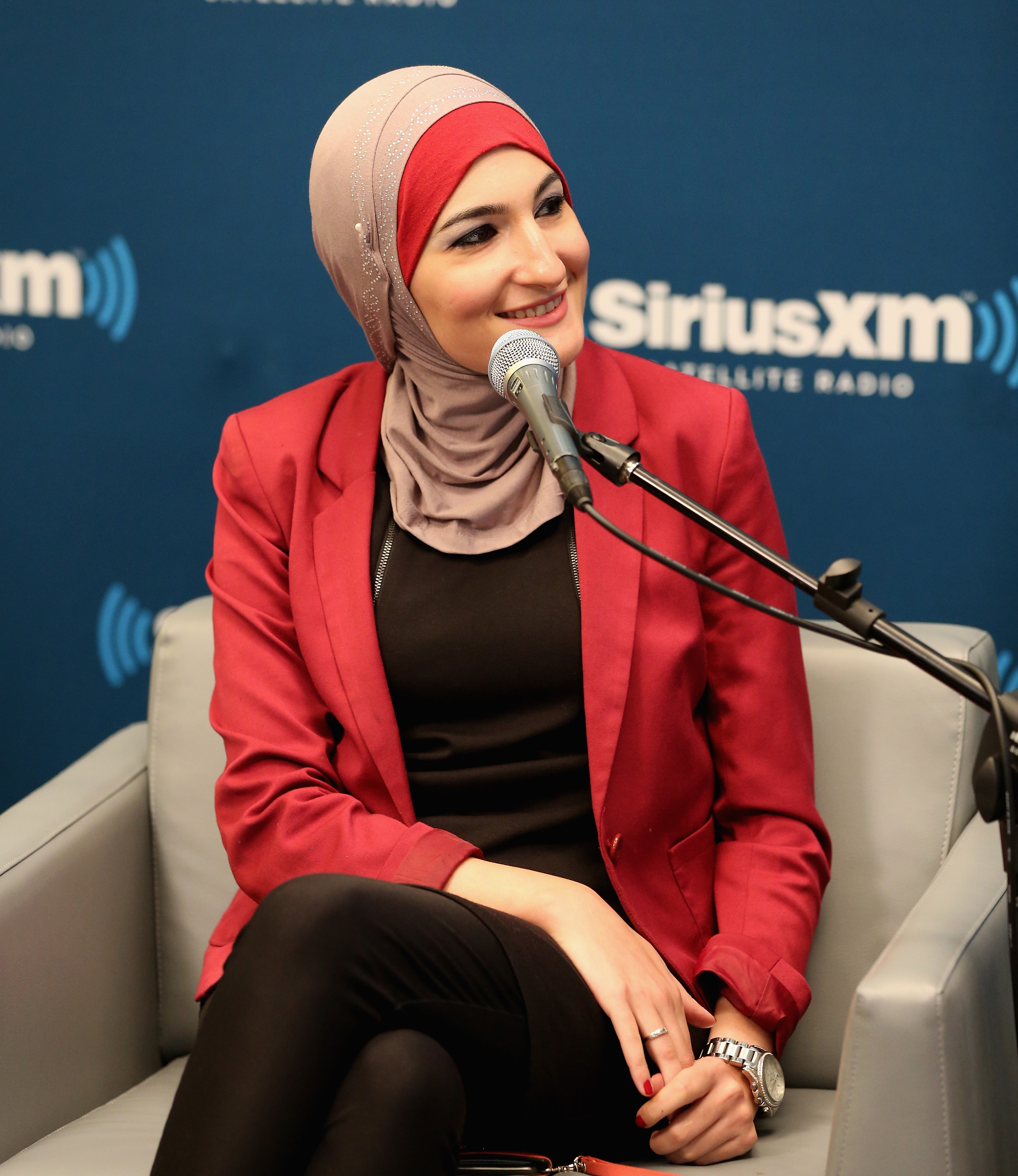 Linda Sarsour wearing a red jacket and head scarf during a SiriusXM event