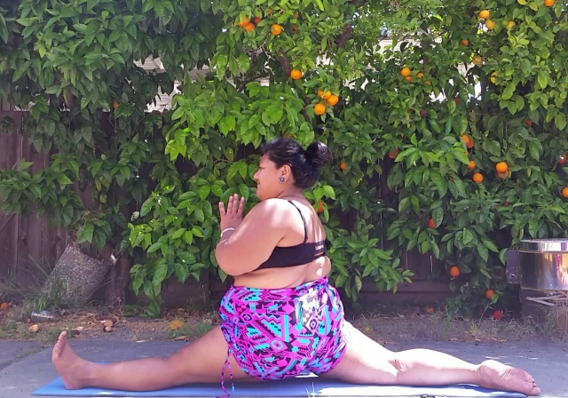 A woman of color doing a split in an outdoor setting