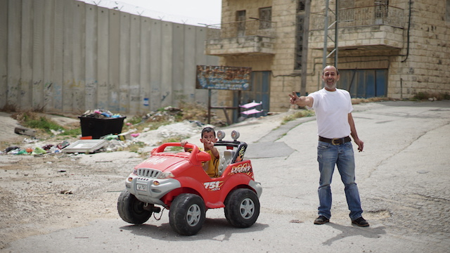 A Palestinian man and his young son, who is sitting a toy car, smile and throw up the peace sign while standing near the separation wall in Bir Nabala, West Bank