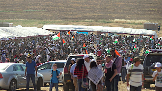 Hundreds of Palestinians, many holding flags, gather in the Naqab Desert in Israel for the 68th Nakba Day.