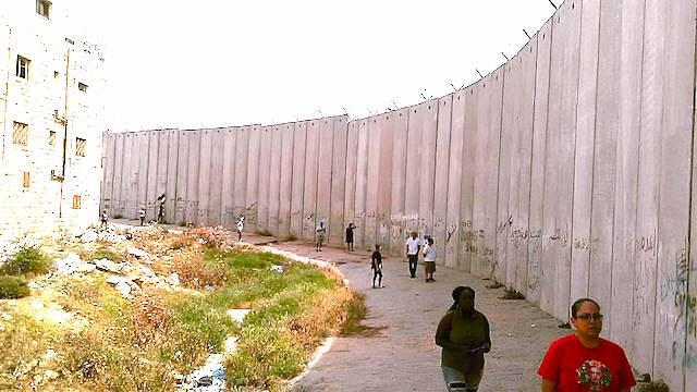 People wearing shorts and T-shirts walk along the thick, tall, concrete separation wall in Bir Nabala in the West Bank.