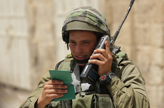 An Israeli soldier wearing green army fatigues and a helmet talks on a walkie-talkie in Hebron.