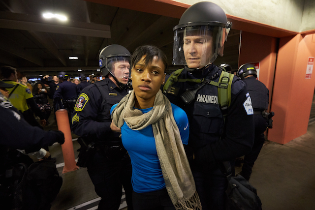 A White officer in riot gear arrests a young Black woman wearing a blue shirt.