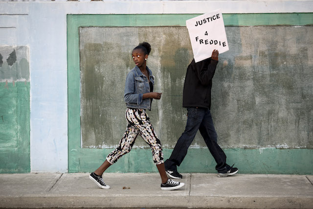 Black teenage holds a Justice 4 Freddie sign while walking with a Black teenage girl to a Baltimore protest