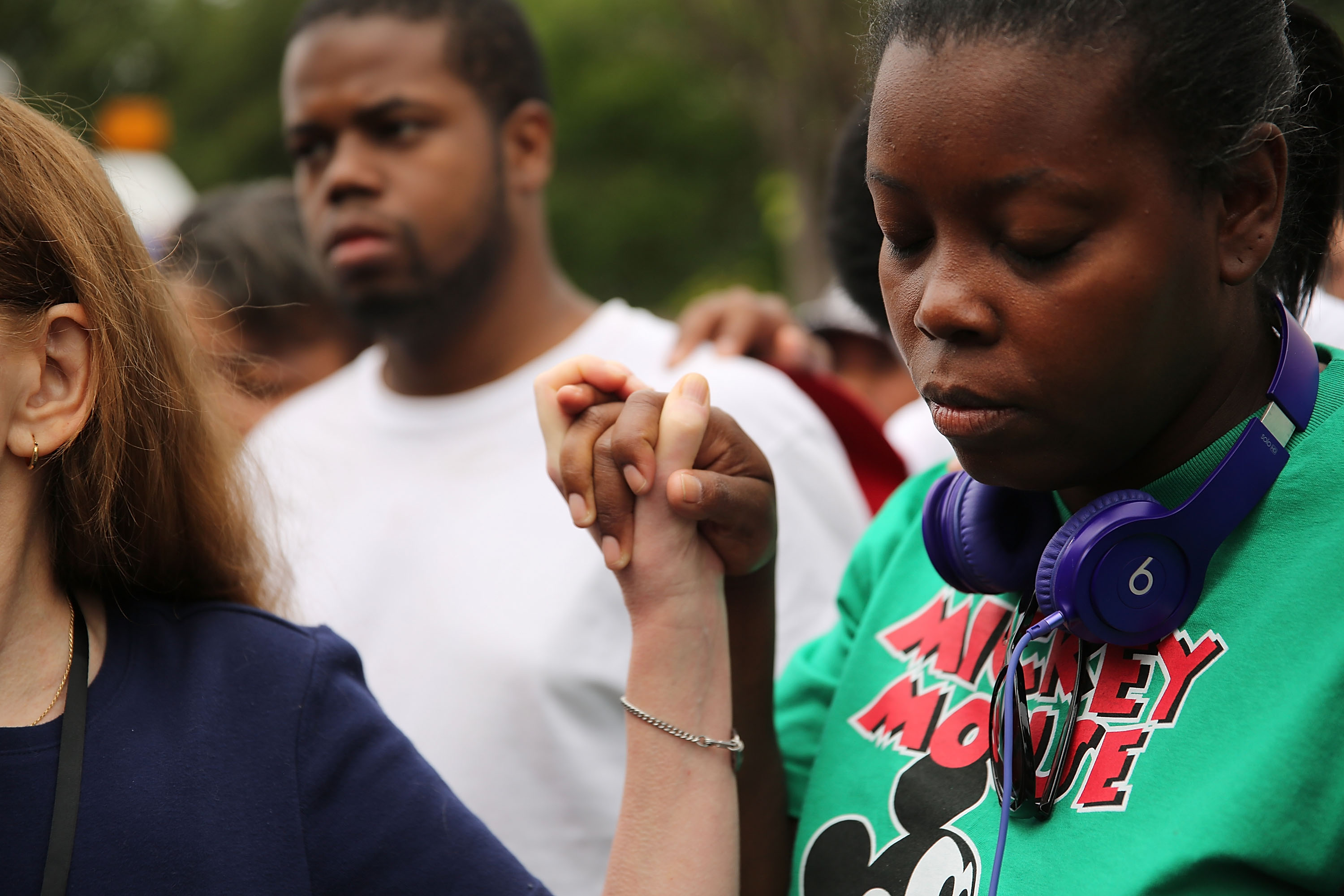 During a prayer, a Black teenage girl wearing a Mickey Mouse T-shirt holds the hand with a White girl during an Eric Garner protest.