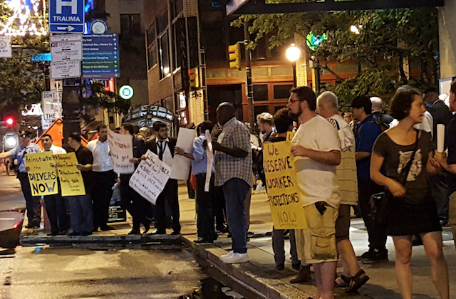 people holding signs on brown sidewalk during nighttime