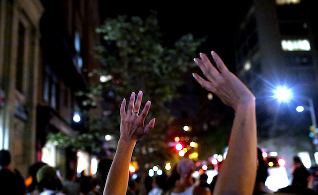 The hands a woman is holding in the air at a nighttime protest