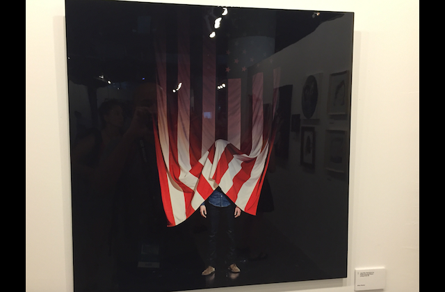 photo with black background and vertical American flag, man's limbs below