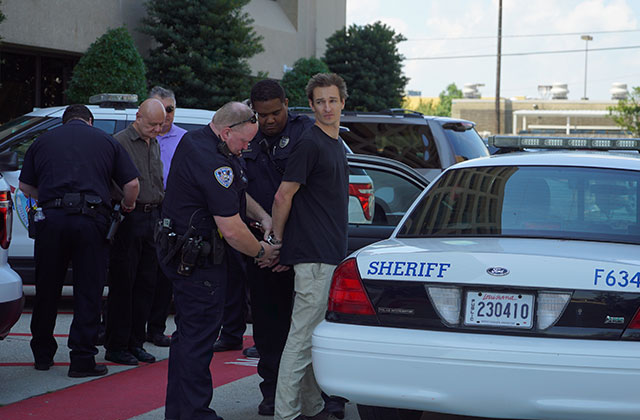 Blake Kopcho, who had to pay a $280 bail, being arrested after protesting for no new leases in the Gulf of Mexico. (Photo courtesy of Laura Cox Tree Media Group)