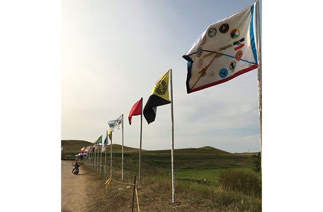 Several tribal flags sit in a line on the Cannon Ball camp in North Dakota, where the Standing Rock Sioux Tribe is protecting its land against the Dakota Access Pipeline.