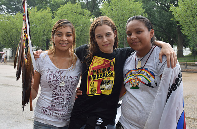 Actress Riley Keough (center) poses with runners Jasilea Rose Charger (left) and Jasilyn Charger  (right) during a break in marching.