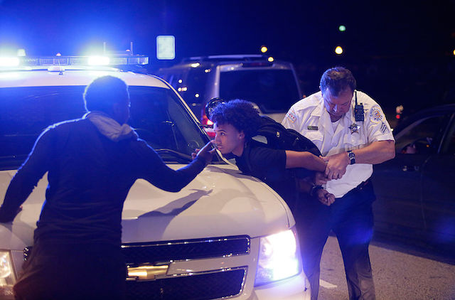 Young Black man being handcuffed on hood of a police car