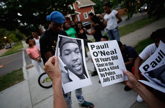 Hands hold fliers with O'Neal's face and death info on them