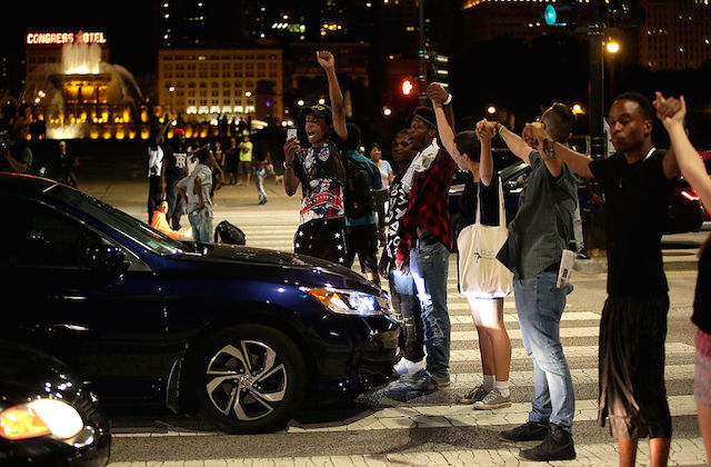 Protesters stand in street, holding hands as they block intersection