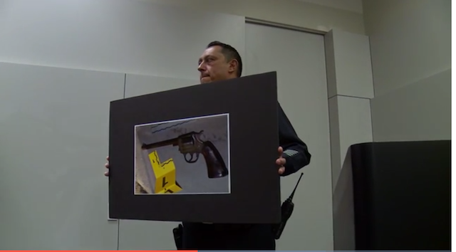 Uniformed LAPD officer holds up a picture of an antiquated handgun at a press conference