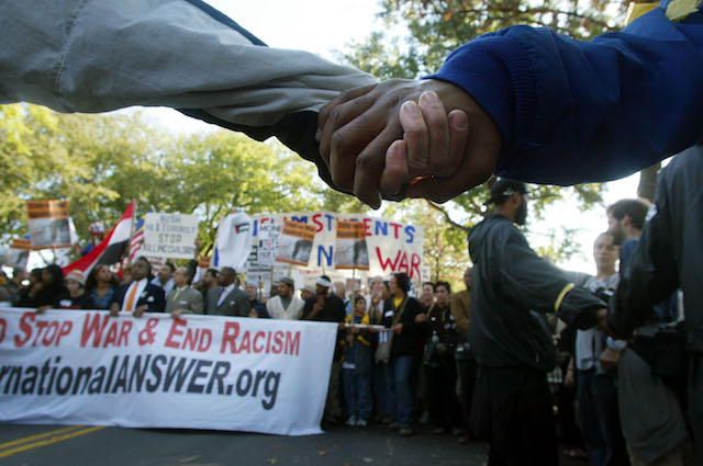 Hands of Black and Brown hands clasped together at anti Iraq war rally in 2002