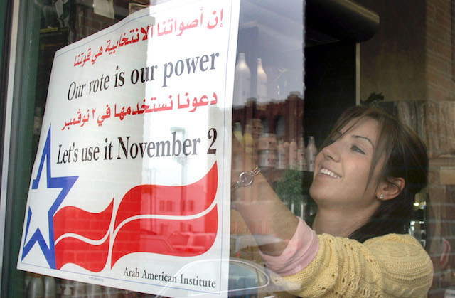 Smiling Arab-American woman posts get-out-the-vote poster in a storefront window