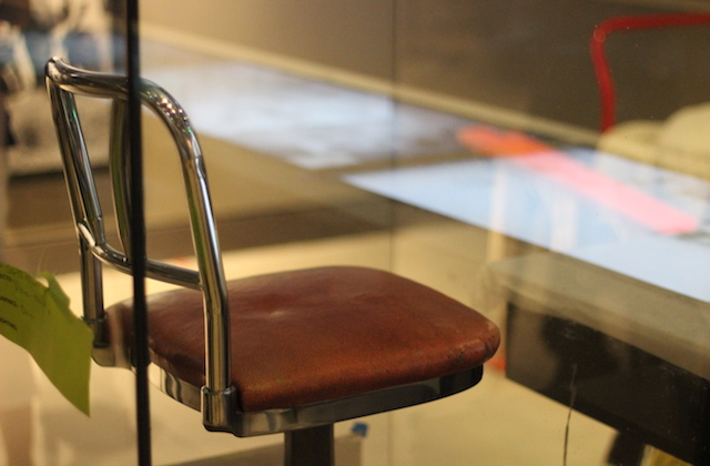 red bar stool with silver metal behind class case