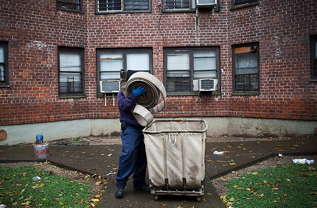 A man lifts up hosing to be used to drain a flooded basement caused by Hurricane Sandy on October 30, 2012, in the Lower East Side neighborhood of New York City.
