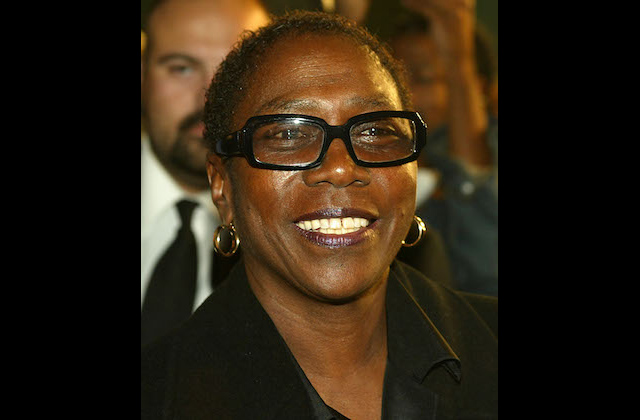 Black woman with black glasses smiling in black blouse against blurry brown background
