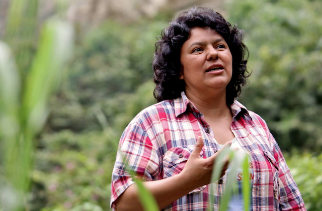 Berta Cáceres in red and white and blue flannel shirt against green foliage