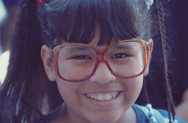 Young Latina wearing oversized amber-colored frames