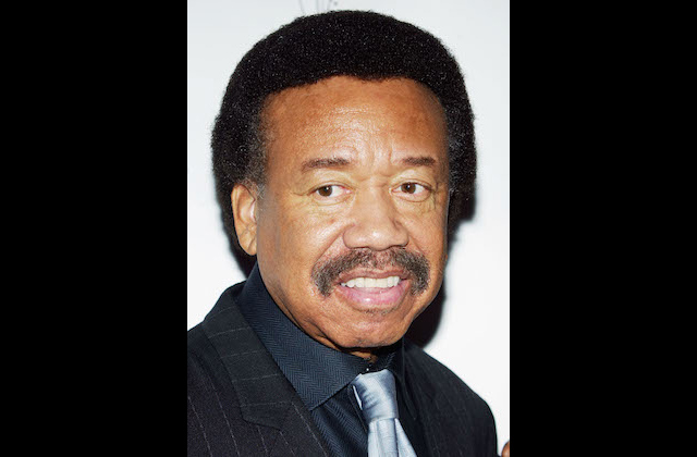Maurice White in a black suit with white pinstripes, navy shirt and blue tie against white background