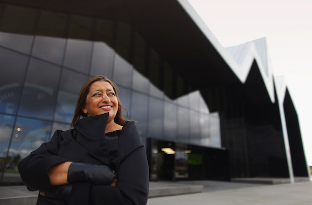 Brown woman in black coat against black glass building and grey sky
