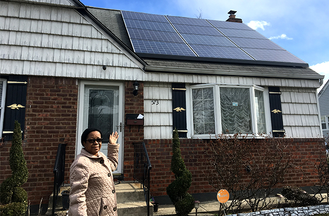Maureen Grogan, 69, points to her solar panels outside her Uniondale, N.Y., home on March 4, 2017, showing off her new source of energy, which is also saving her money every month.