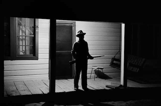 Black-and-white image of Black man in hat and holding rifle on dimly lit house porch with black door