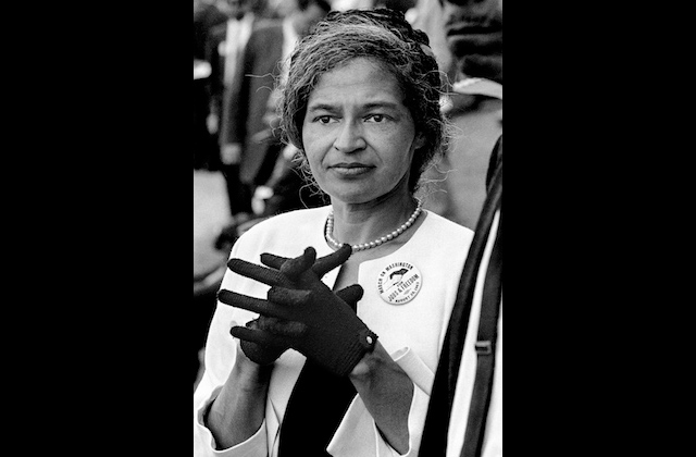 Black-and-white image of a Black woman in dark gloves and a light-colored blouse in front of grey blurry background