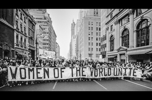 Black-and-white image of women holding white banner with black letters on grey pavement between buildings