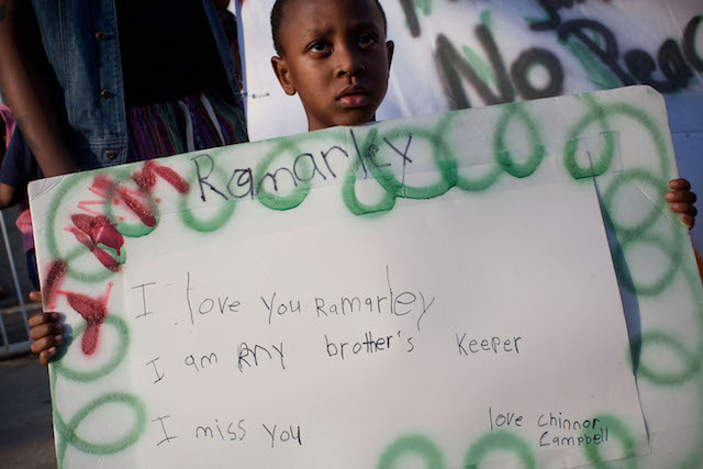 A young boy, Chinnor Campbell,  holds a handwritten sign that reads,