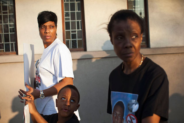 A woman in a white T-shirt, Constance Malcolm,  a young boy, Chinoor Campbell, and an elderly woman, Patricia Hartley, look toward a camera after a march