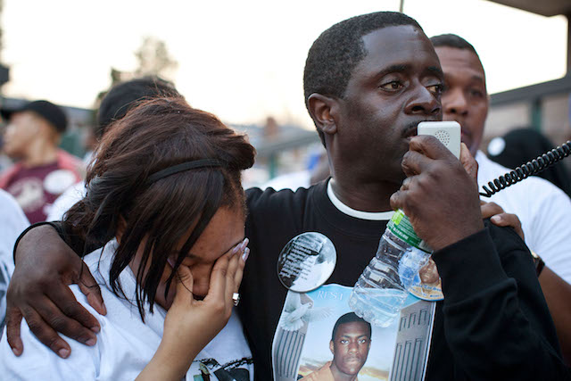 Franclot Graham, wearing a black T-shirt with a photo of his slain son, speaks into a microphone