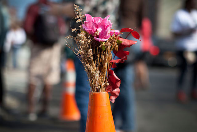 A pink flower bouquet sits on top of an orange construction cone