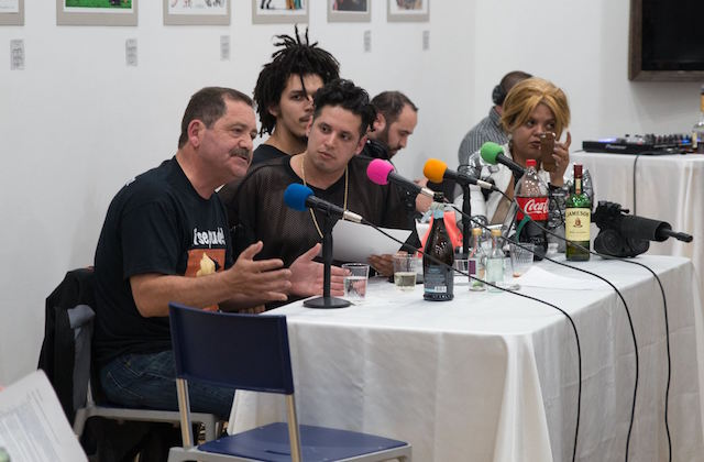 Brown and black people sit at table with black microphones and white tablecloth and multicolored microphone covers in front of white wall with multicolored artwork