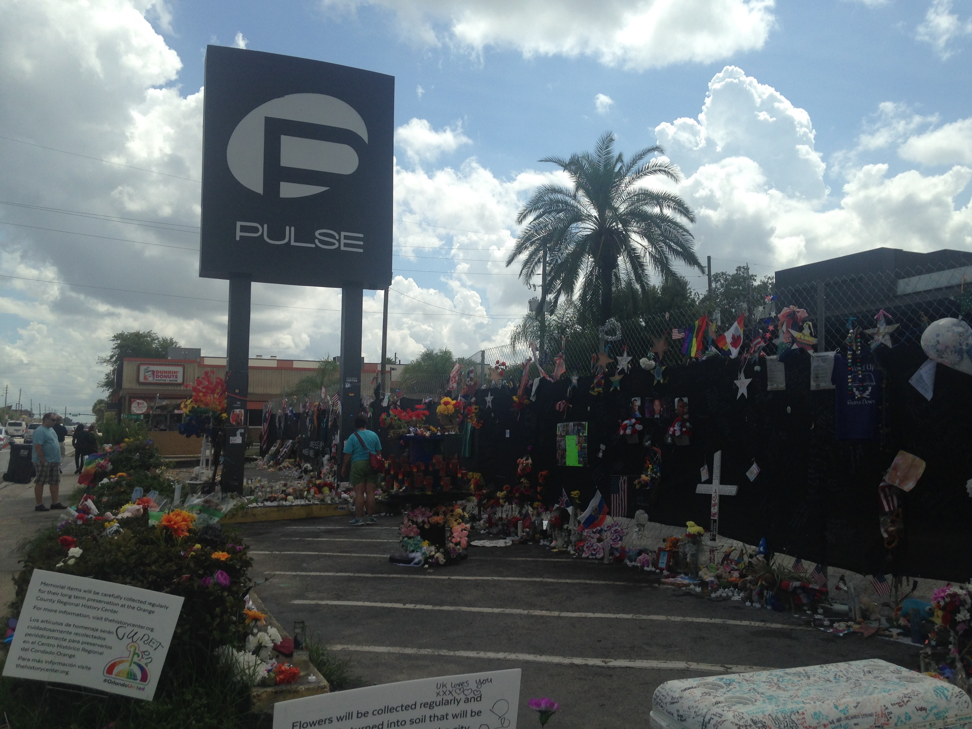 A photo of the Pulse nightclub sign with candles and other memorial items collected