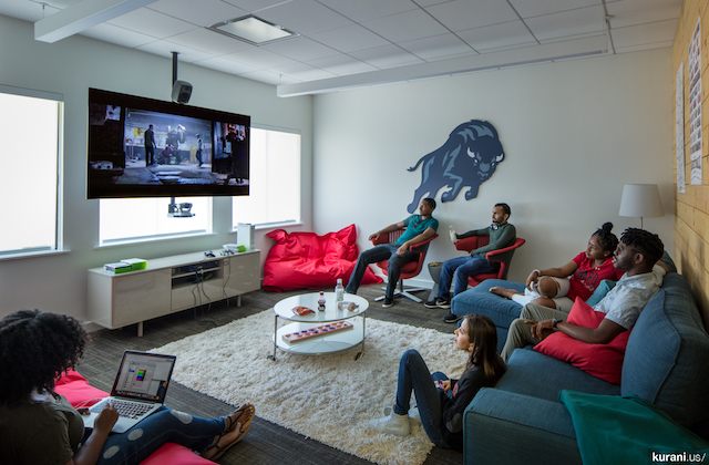 Black women and men sit on red chairs and pillows and blue couch in front of black television in room with white walls and brown carpet with white rug and grey bison on wall