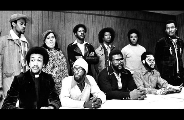 Black-and-white photo of Black men and White woman in multicolored clothing seated and standing in two rows