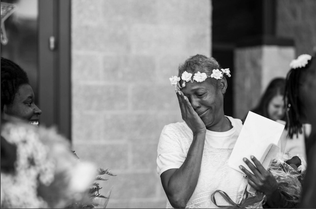 A Black woman with a wreath of flowers around her head wipes away tears as she exits Pinellas County Jail in Clearwater, Florida, on May 11, 2017.